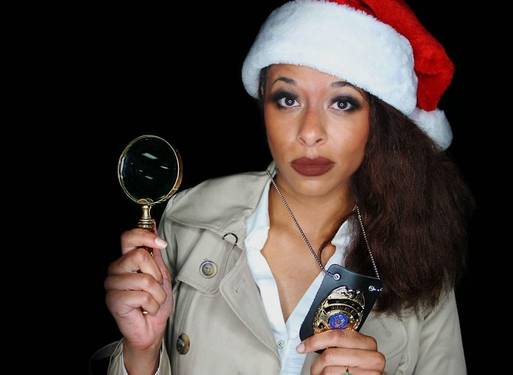 Murder mystery detective in a white and red santa hat posing with a badge and magnifying glass