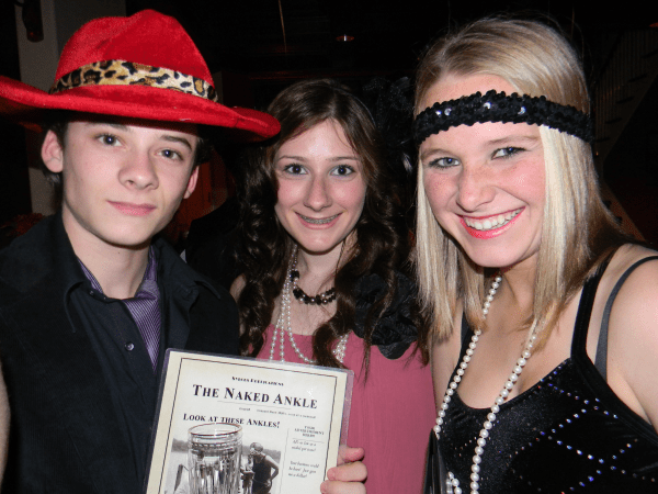 three teenagers in 1920s apparel posing for a photo during a murder mystery barmitzvah event.