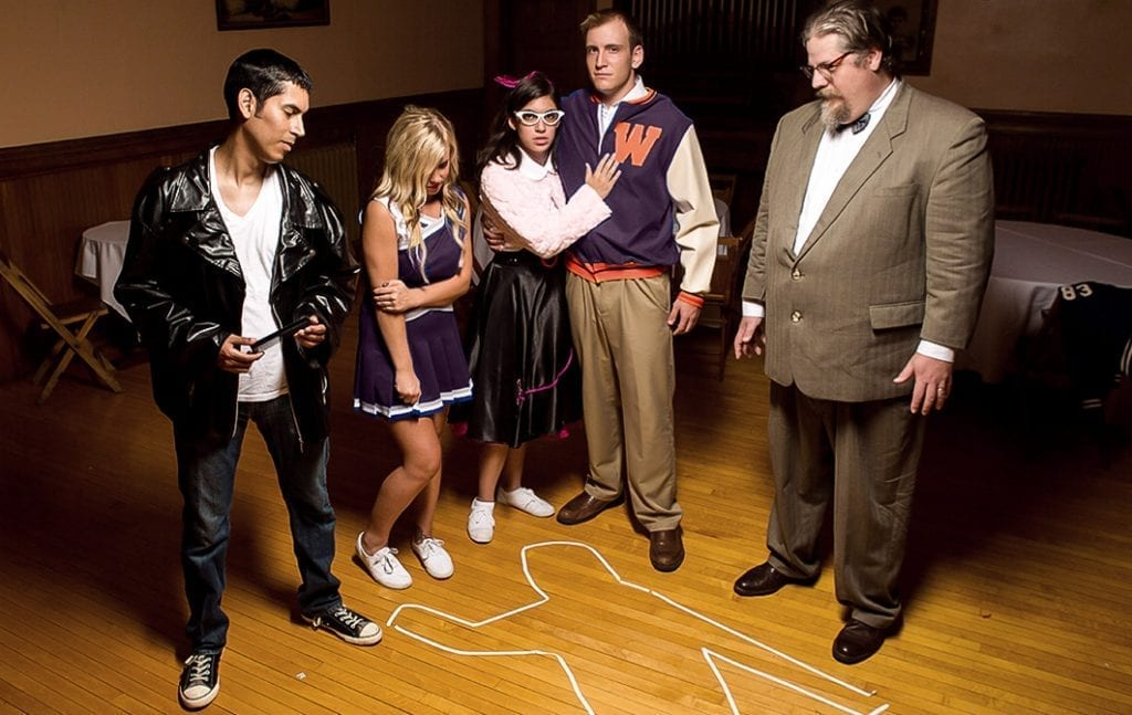 4 students and a professor investigating crime scene in a school gymnasium.