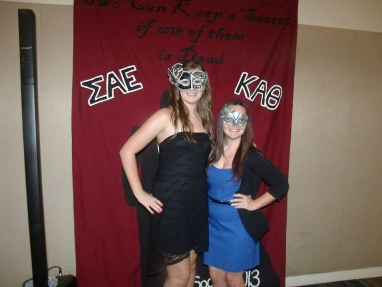 Two girls pose in masquerade apparel during a murder mystery sorority event.